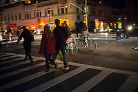 As night falls New Yorkers cross an intersection in Chelsea in New York by the light of automobile headlights on Wednesday, October 31, 2012. The New York subway system is still not operating but the Metropolitan Transit Authority has buses up and running and is not collecting fares. The subway will begin operating with limited service tomorrow. (© Richard B. Levine)