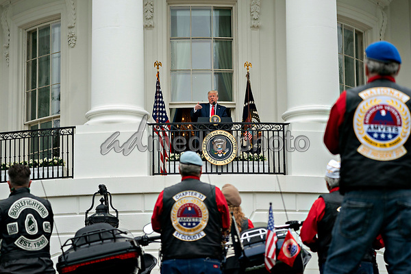 United States President Donald J. Trump, center, speaks from the Blue Room Balcony of the White House during a Rolling to Remember ceremony honoring the nation's veterans and prisoners of war/missing in action (POW/MIA) in Washington, D.C., U.S., on Friday, May 22, 2020. Trump didn't wear a face mask during most of his tour of Ford Motor Co.'s ventilator facility Thursday, defying the automaker's policies and seeking to portray an image of normalcy even as American coronavirus deaths approach 100,000. <br /> Credit: Andrew Harrer / Pool via CNP/AdMedia