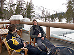 Two young men relax with drinks by a fire pit on the deck at  Resort at Squaw Creek, Squaw Valley, CA at Lake Tahoe
