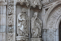 2 statues under canopies flanking the doors, on the South Portal, 1516-18, by Joao de Castilho, 1470ñ1552, after a design by Diogo de Boitaca, Church of Santa Maria, at the Jeronimos Monastery or Hieronymites Monastery, a monastery of the Order of St Jerome, built in the 16th century in Late Gothic Manueline style, Belem, Lisbon, Portugal. The portal consists of double doors with a tympanum carved with scenes from the life of St Jerome, a statue of Henry the Navigator, many carved statues in niches, a statue of the Madonna and many flamboyant pinnacles and gables in Manueline style. The monastery is listed as a UNESCO World Heritage Site. Picture by Manuel Cohen