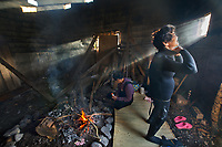 """Hisae, 'Ama' Free-Diver, Sea Women, Osatu, Mie Prefecture, Japan, 2016<br /> It is considered that the Japanese practice of 'ama' traditional free-diving has been passed down through female generations for about 2000 years. These women collect seaweed, conch, lobster, abalone and shellfish. They became more in demand with the discovery of the cultured pearl in 1893, giving them the name """"ama pearl divers."""" In the early morning hours these women, who until recently wore only a loincloth, apply oil and warm themselves by the fire in the warming hut to prepare for a day of diving in frigid waters. The men drive the boats and help haul the catch, but the women are considered to be better divers due to the distribution of their fat and their ability to hold their breath. Most of the women remaining in this job are now well into their 70s and are thought to live longer due to their diving training and disciplines. Hisae Okano, shown here, is 75, and as third-generation divers, these women are probably the last. The younger women in the village don't want to pursue this profession and have moved to the cities to find more modern occupations."""