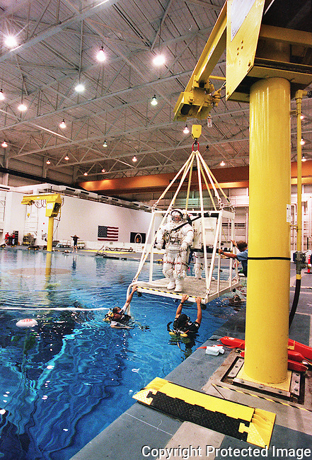 ADVANCE FOR SUNDAY--NASA mission specialist Claude Nicollier, of Switzerland, and fellow mission specialist Michael Foale are lowered into  a 40' deep pool at NASA's Neutral Boyancy Laboratory (NBL), in houston, Texas, Friday, Sept. 10, 1999, for a training simulation in repairing the Hubble Space Telescope.  NASA uses the pool to simulate a weightless environment enabling crews to work with full-scale mock ups prior to the actual mission.(Brian Myrick)