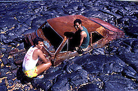 Two men near old rusted car embedded in pahoehoe lava bed. Hawaii volcanoes national park, Big island