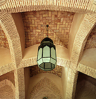 A Moroccan lantern hangs from the vaulted brick ceiling