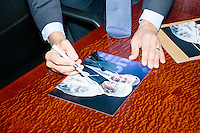 Democratic presidential candidate and former governor of Maryland Martin O'Malley signs photos of himself and Bill Clinton which an autograph dealer intends to sell on eBay after O'Malley spoke at a small town hall event at McLane law firm in Manchester, New Hampshire. The firm holds a town hall series, inviting candidates to speak at their headquarters.