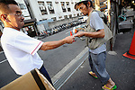 An unemployed man is handed a food ticket outside one of the shelters in the Kamagasaki district of Osaka, Japan. Thousands of homeless people flock to the Kamagasaki district daily in hope of securing day labor work, such as hands on building sites - jobs that pay around $US70 pounds per day, and a bed for the night