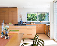 A modern, open plan kitchen with bleached walnut cabinets by Olive Square Kitchens with Caesarstone counters. The floor is stained ash. A gas hob is set in a central island unit. Two old fashioned oil lamps are arranged on a breakfast table.