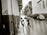 PANAMA, Panama City, children playing in the rain in the street (B&W)