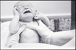 gloved hands holding crying newborn baby
