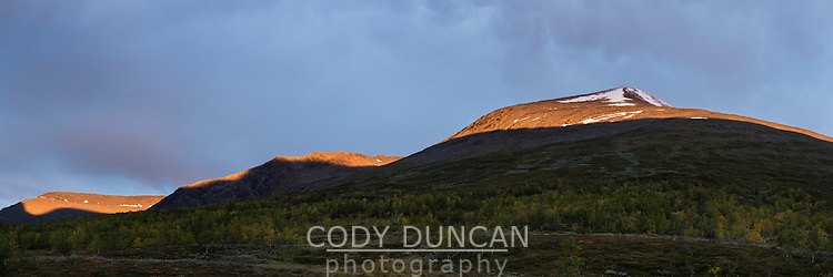 Mountain peaks catching first rays of light above Kaitumjaure mountain hut, Kungsleden Trail, Lapland, Sweden