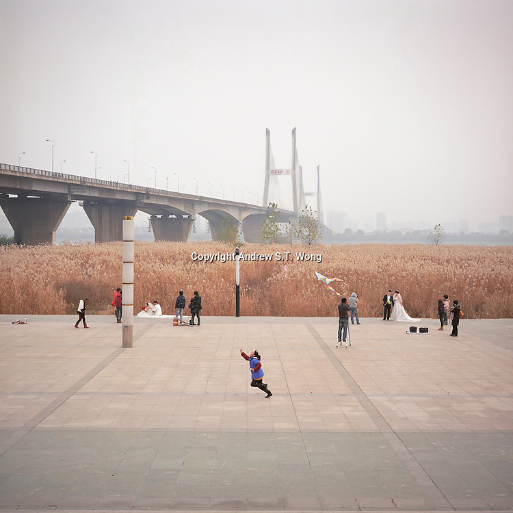 A girl runs with a kite as newlyweds have their photos taken in front of a wall of reeds along the riverbank of Chang Jiang, or Yangtze River, in Wuhan, Hubei province, December 2011. Wuhan's second Yangtze River Bridge is seen in the background. (Mamiya 6, 75mm f3.5, Kodak Ektar 100 film)