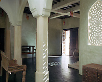 The hot African sun is filtered through the delicate latticework screens of the arched windows in the entrance hall