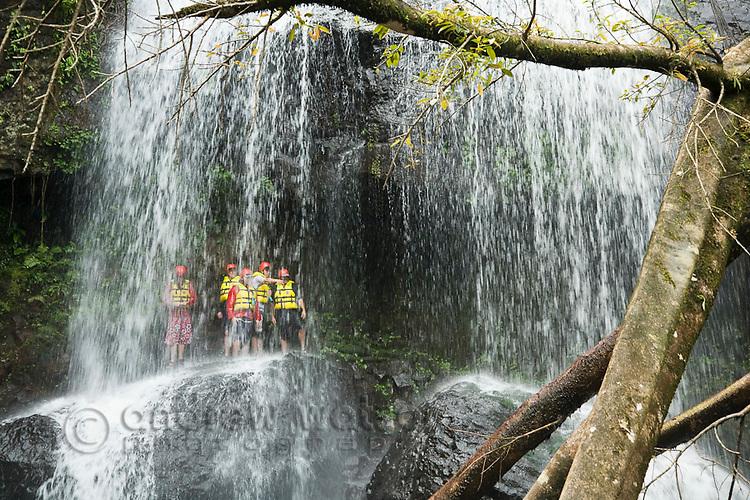 Group standing underneath rainforest waterfall.  North Johnstone River, Wooroonoonan National Park, Queensland, Australia