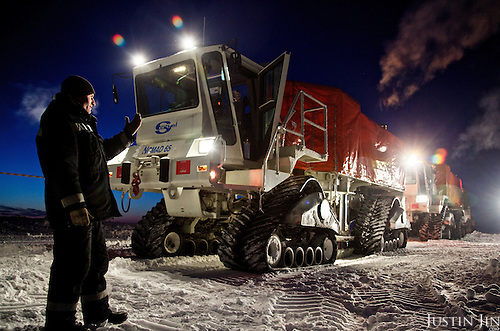 """A worker from gas and oil exploration company """"Seismorazvedka"""" guides an all-terrain """"Vibrator"""" in the Arctic tundra in the Nenets Autonomous Region. The vehicle, made by French company Sercel, uses seismic vibration to test the structure of the earth crust below to help prospect for oil and gas. Billions of tonnes of gas and oil have been found in the region in the last decade."""