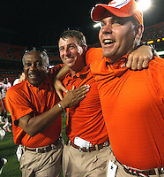 Clemson coach Dabo Swinney, center, hugs team administrator Woody McCorvey, left, and assistant coach Danny Pearman, right, after the Tigers beat Miami 40-37 in overtime Saturday.