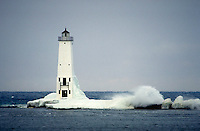 Winter ice and waves on Frankfort North Breakwater Lighthouse. Frankfort Michigan USA Lake Michigan.