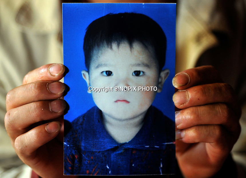 Mao Zheng Fa, holds a photograph of his daughter, Mao Ying Die, aged four, when stolen 16th March 2008, from the suburbs of Kunming city.  Girls in China are increasingly targeted and stolen as there is a shortage of wives as the gender imbalance widens with 120 boys for every 100 girls..PHOTO BY SINOPIX
