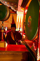 Buddhist Monk playing drums in a Losar ceremony inisde a monastery, Sikkim, India