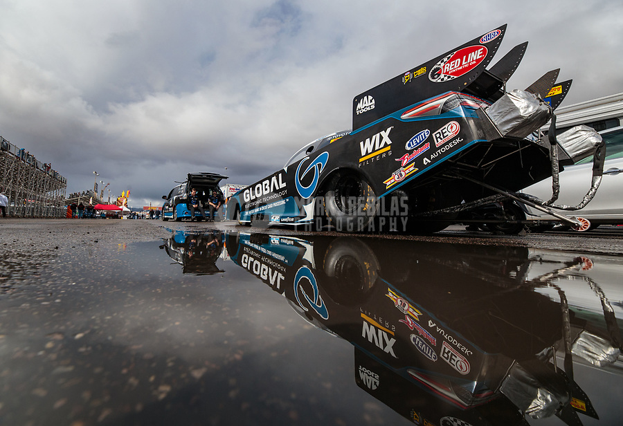 Feb 22, 2019; Chandler, AZ, USA; The car of NHRA funny car driver Shawn Langdon reflects in a rain puddle as the car is towed to the staging lanes during qualifying for the Arizona Nationals at Wild Horse Pass Motorsports Park. Mandatory Credit: Mark J. Rebilas-USA TODAY Sports