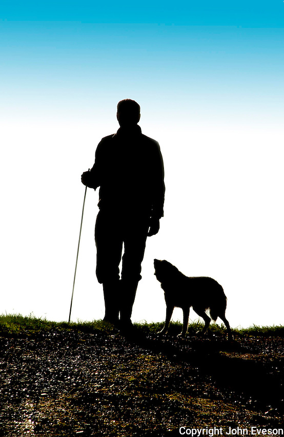 Shepherd and Sheepdog in silhouette.