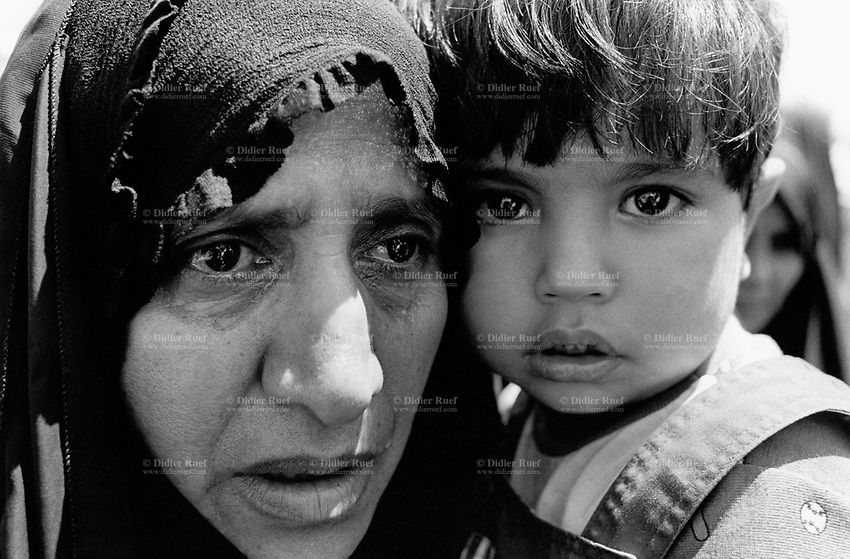 "Iraq. Baghdad. A mother holds her young daughter in her arms. The "" Committee for free prisoners"" establishes various lists of the people which were executed by Saddam Hussein regime. Families come everyday to read the lists and collect informations on their loved parents, hoping to know their whereabouts. © 2003 Didier Ruef"
