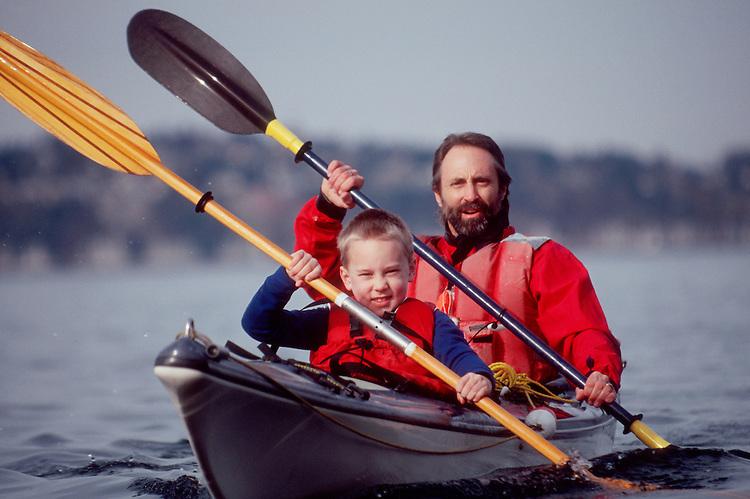 Sea Kayaking, Man and son sea kayaking in a double kayak , Seattle, Puget Sound, Washington State, Pacific Northwest,.