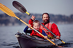 Sea Kayaking, Man and son sea kayaking in a double kayak , Seattle, Puget Sound, Washington State, Pacific Northwest,.