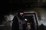 A member of the Hamayel family inspects the damage to her home, that was attacked and burnt by suspected Jewish extremists using petrol bombs, in the village of Abu Falah, northeast of Ramallah, on November 23, 2014. Suspected Jewish extremists firebombed a house in a Palestinian village in the occupied West Bank early, its mayor said, pointing the finger of blame at local settlers. Masud Abu Mura, mayor of Khirbet Abu Falah, said four women were inside the house at the time, but they all escaped unharmed. Photo by Shadi Hatem