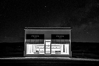 Another capture of the Prada Marfa in black and white at night with a starry night skie.  In this Prada Marfa image the sky is full of stars over the store front along the road on a dark highway in far west texas. The one thing about this area of west Texas is its wonderful dark skies where you can actully see and capture stars in your images. The road between Marfa and Valentine was so dark we thought we might have missed it because it was so dark, but finally, there it was just feet from the road in all it glory waiting for the next photo or selfie, that seems to draw people out here. The permanet exhibit was created by two artist Elmgreen and Dragset in October 2005 to resemble an actual Prada store. The two refer to their work as pop architectual land art with a bit of humor. They built this structure about 24 miles outside of Marfa in a city called Valentine Texas population around 200. To make it more interesting they found the least likely place to find a store like this and stuck in in far west texas. They added only right shoes and the purses have no bottoms. They have been vandalize several times now I guess people in this area like prada more than they knew. I am not sure what they were saying or not saying about their art. Maybe they were making fun of consumerism but you would have to ask them. As a photographer it great fun to shoot such a unique image. After the latest vandalism they have install cameras and the purses have GPS devices inside that detect movement so making it more difficult to shop there in the future. We had been to see the Marfa Lights many times but never venture over to Valentine to see the Prada Art display and we were glad we finally made it. Having this wonderful starry night sky really helped it pop out as a winning venture for us.