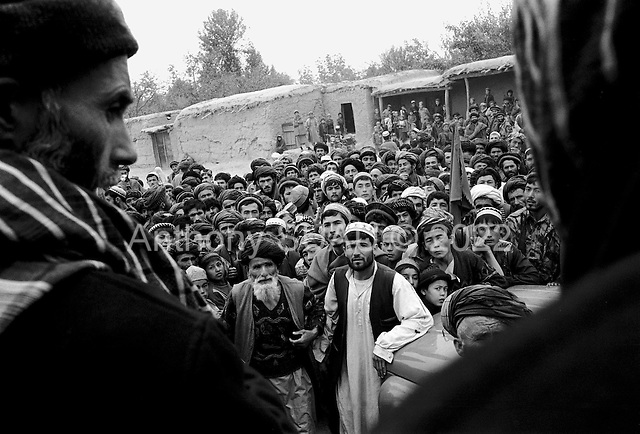 Northern Afghanistan<br /> October 2001<br /> <br /> 31 year old American John Weaver distributes the last of Canadian donated oil for Shelter for Life and the World Food Program to a small crowd in a square near the Nowabad refugee camp.