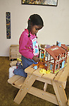 Berkeley CA Girl, three-years-old, in fantasy play with doll house in her bedroom