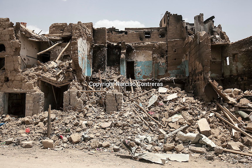 """Wednesday 15 July, 2015: Blocks of house-buildings are seen downed to the ground in a market place in the downtown of Sa'dah, a city subdued to heavy bombardments carried out by the Arab states and their western allies led by Saudi Arabia in the northern province of Sa'dah, the stronghold of the Houthi's movement declared unilaterally """"a military zone"""". The historic city of Sa'dah is among the places submitted on a tentative list to be under protection of UNESCO as a World Heritage site like the others enlisted cultural heritage sites in Yemen, such as the historic town of Zabid, the Old City of Sana'a and the Old Walled City of Shibam endangered by the ongoing aerial campaign of bombardments. (Photo/Narciso Contreras)"""