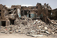 "Wednesday 15 July, 2015: Blocks of house-buildings are seen downed to the ground in a market place in the downtown of Sa'dah, a city subdued to heavy bombardments carried out by the Arab states and their western allies led by Saudi Arabia in the northern province of Sa'dah, the stronghold of the Houthi's movement declared unilaterally ""a military zone"". The historic city of Sa'dah is among the places submitted on a tentative list to be under protection of UNESCO as a World Heritage site like the others enlisted cultural heritage sites in Yemen, such as the historic town of Zabid, the Old City of Sana'a and the Old Walled City of Shibam endangered by the ongoing aerial campaign of bombardments. (Photo/Narciso Contreras)"