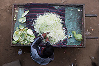 A street vendor chops cabbage on the sidewalk at HUDA City Centre in Gurugram, Haryana, India, on Mon., December 10, 2018.