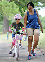NWA Democrat-Gazette/DAVID GOTTSCHALK Jessica Danley helps guide her daughter Eve, 6, Monday, August 6, 2018, as she rides with a basket full of stuffed animals on her first attempt to ride without training wheels at Gulley Park in Fayetteville. The Fayetteville Parks and Recreation Advisory Board on Monday will go over the proposed master plan for Gulley Park. Suggested amenities include an activity hub for children, a splash pad and a dog park.