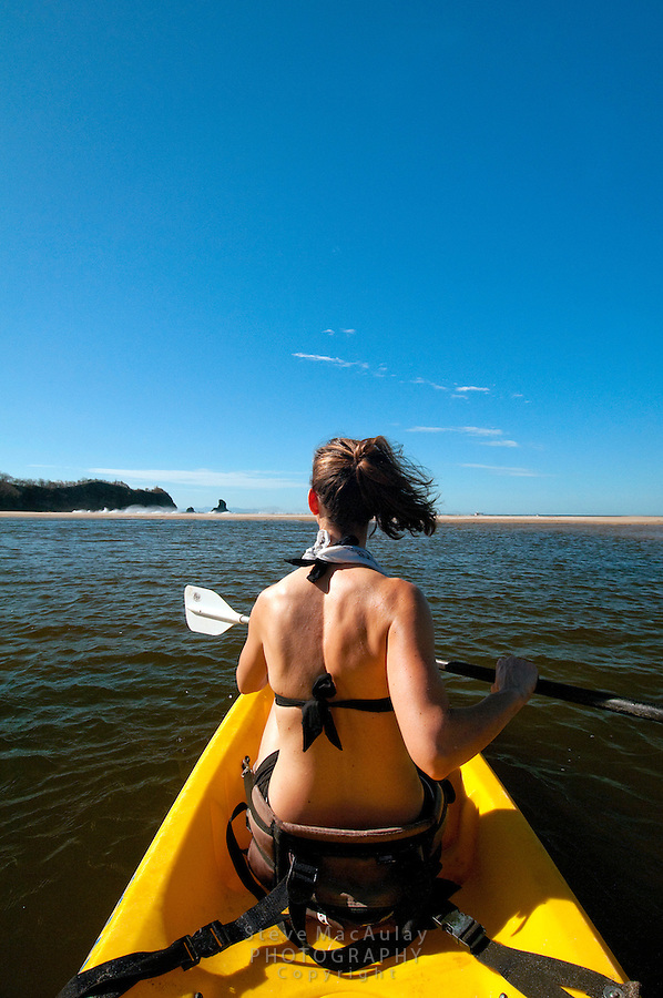 Young woman paddling a sea kayak in river estuary approaches the coastline, Morgan's Rock Hacienda and Eco Lodge, Nicaragua