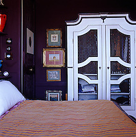 A white-painted wardrobe in the bedroom contrasts with the deep purple walls