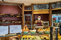 Commessi della panetteria Manon di Saint Paul Paris , con mascherina  Bread shop in Paris Interno di panetteria Il commesso con mascherina protettiva