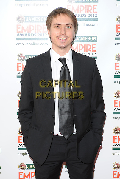 Joe Thomas .Jameson Empire Film Awards at the Grosvenor House Hotel, Park Lane, London, England..March 25th 2012.half length black suit blue shirt tie hands in pockets .CAP/BF.©Bob Fidgeon/Capital Pictures.