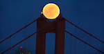 The full moon sits on top of the North Tower of the Golden gate Bridge during the evening twilight in San Francisco, California.