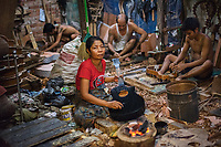 Nyunt Yee, Guitar Factory, Yangon, Burma 2016<br /> Daw Nyunt Nyunt Yee runs a guitar-building shop in Yangon, thanks to a loan she received for supplies. The air is thick and smells of chemicals as the heavy varnish, paint, and glue are heated over a fire in a room with no ventilation. The room crowded with about sixteen workers, who can make about 200 guitars a week. The dealer pays about $15 a piece. Nyunt makes about $400 per week take-home pay, which helps support her 8-year-old child, a student.