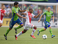 Darlington Nagbe of the Portland Timbers, center, dribbles the ball in front of Leonardo Gonzalez of the Seattle Sounders FC during play at CenturyLink Field in Seattle Saturday August, 3, 2013. The Sounder won the match 1-0.