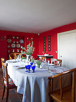 A collection of Spanish plates is displayed against the warm red of the dining room walls
