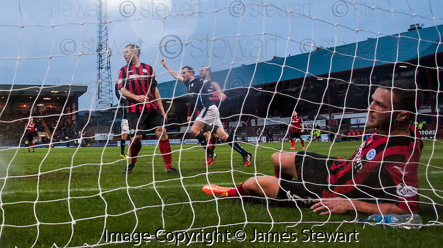 Dundee's David Clarkson celebrates as St Johnstone's Chris Millar lies in the back of the net.