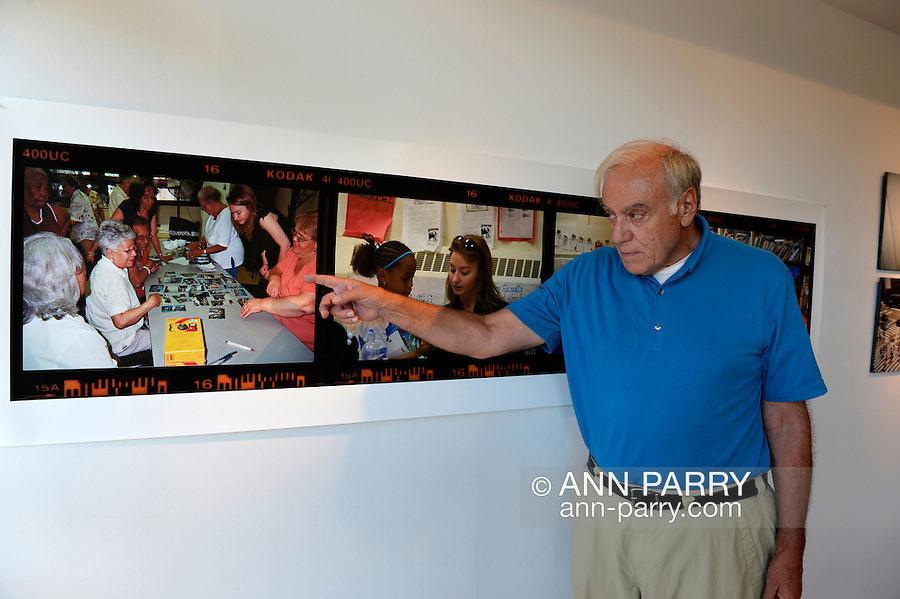 GEORGE CARRANO points to photos documenting photo project at the Reception for Project Lives exhibition at fotofoto gallery. Over 200 residents throughout 15 New York Public Housing projects were given single use film cameras to photograph what's important to them in their world. The photography project was originated by Carrano, and the book Project Lives was edited by Carrano, Chelsea Davis who is at right in photo above Carrano's arm, and Jonathan Fisher, and all royalties from its sale are to be donated to resident programs at NYC Housing Authority. The gallery is on the Gold Coast of Long Island.