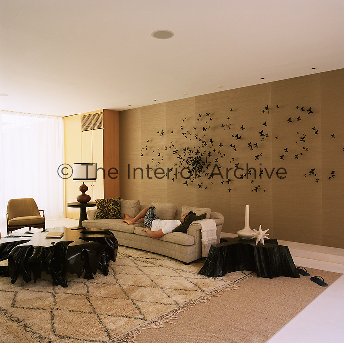 A man reclines on a curved sofa beneath a large butterfly installation by Paul Villinski that is mounted on the wallpapered wall of the living room