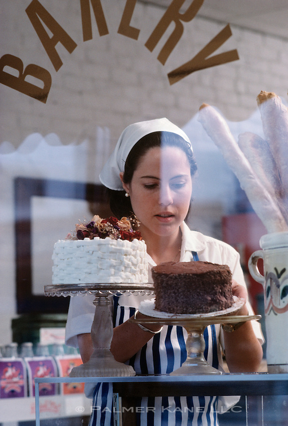 Bakery clerk putting a cake in the window of retail shop