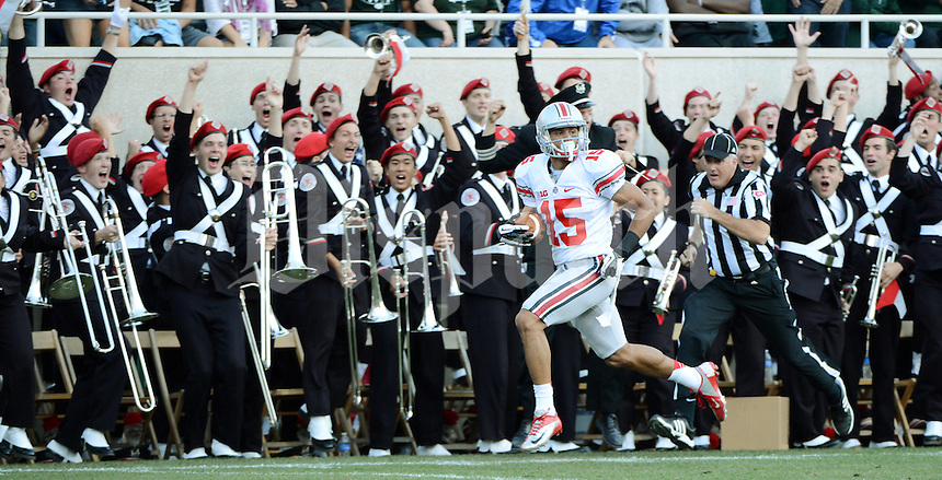 Ohio State Buckeyes wide receiver Devin Smith (15) makes his way down the sideline past the Ohio State marching band on his way to scroring the go ahead touchdown against the Michigan State Spartans  in the thrid quarter of their NCAA football game at Spartan Stadium, September 29, 2012.   (Photo by Neal C. Lauron)