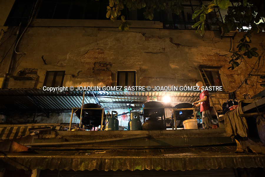 A man cooks at night on the roof of his house in the old quarter of Hanoi (Vietnam)<br /> HANOI-VIETNAM