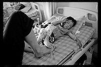 A Tibetan boy listens to music as he rests with his father after a cleft palate operation organized by Smile Angel Foundation at a hospital in Xining, Qinghai province, China, August 2013. (Names withheld for privacy)